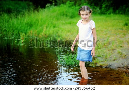 Adorable brunette school aged girl wearing a jeans skirt and t-shirt playing at a river shore on a hot sunny summer day - stock photo