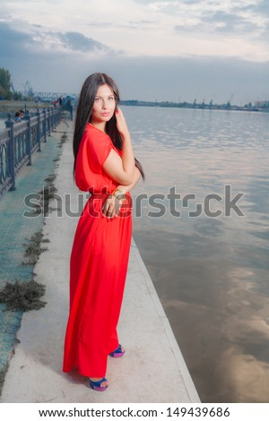 Adorable brunette Smiling with red dress posing on a dawn looking away. Fashion Beauty. Outdoors shot near river. Side view - stock photo