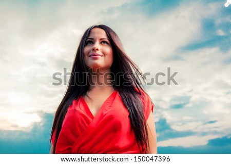 Adorable brunette with red dress posing on a dawn. Fashion Outdoors shot. - stock photo