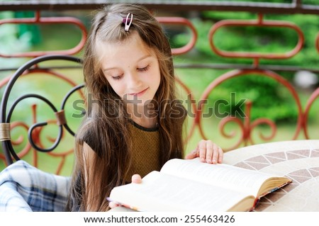 Adorable brunette young schoolgirl reading a colorful book on the balcony on summer day - stock photo