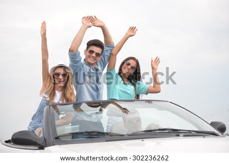 Adorable car trip on vacation. Group of happy friends driving by cabriolet with hands up. - stock photo