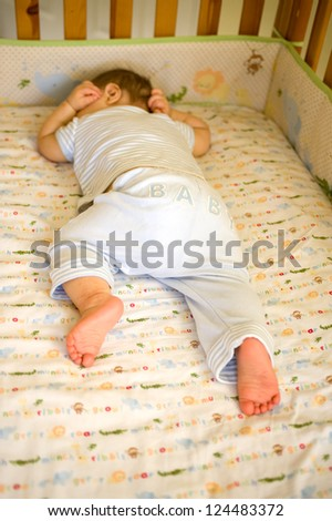 Adorable Caucasian baby boy sleeping in his crib on jungle animal bedding - stock photo