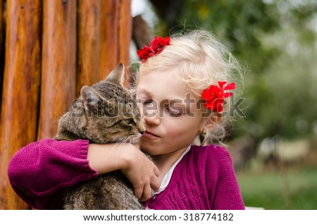 adorable caucasian blond girl holding domestic cat  - stock photo