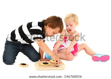 Adorable Caucasian brother and sister sitting on floor with cook - stock photo