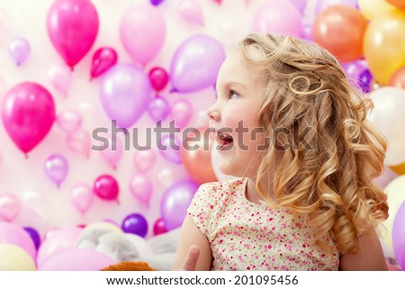 Adorable cheerful girl on balloons background - stock photo