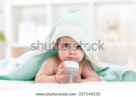 Adorable child baby drinking water from bottle. Little girl  wrapped bathing towel lying on bed. - stock photo