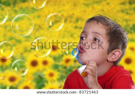 adorable child blowing soap bubbles in a field of flowers - stock photo