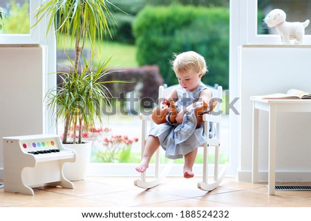 Adorable child, curly blonde toddler girl playing indoors with doll sitting on a rocking chair in white sunny room with big street view window