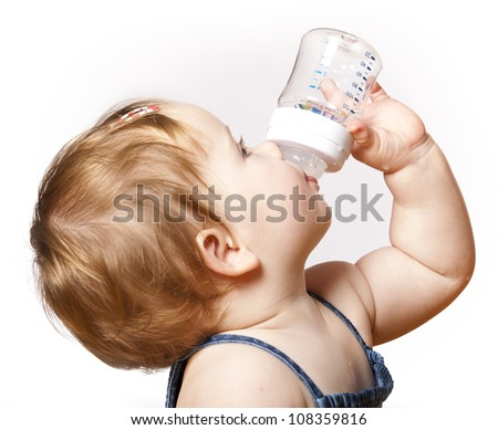 adorable child drinking from bottle. 10 months old girl. - stock photo