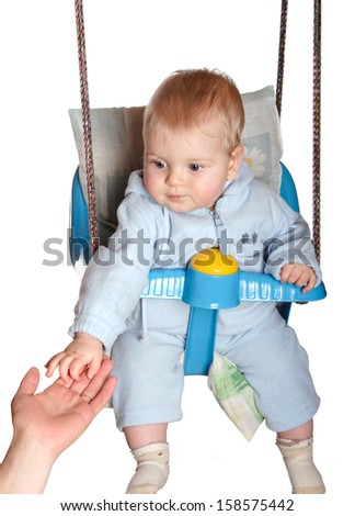 Adorable child hang on swing and catch his mother's hand - stock photo