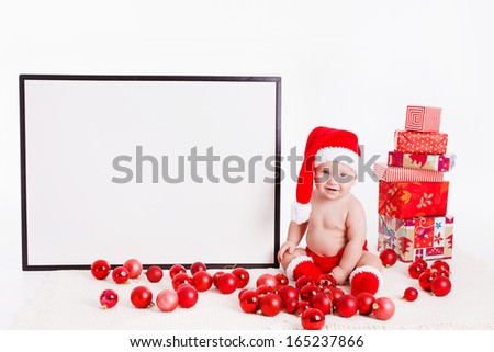 Adorable child is sitting on floor, wearing red Christmas cap, red balls and presents around. isolated on white background - stock photo