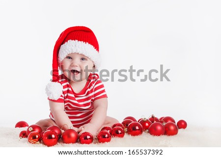 Adorable child is sitting on floor, wearing red Christmas cap, red balls around. isolated on white background - stock photo