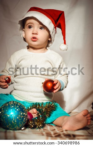 Adorable child is sitting on floor, wearing red Christmas cap, red balls around. isolated on white background,vertical photo - stock photo