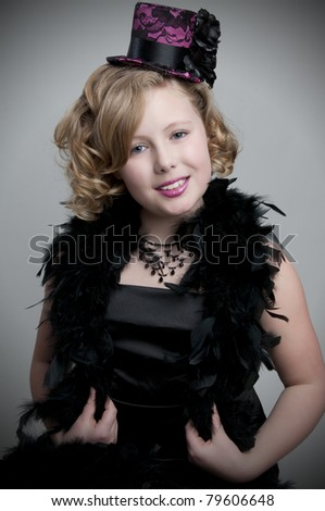 Adorable child model wearing feather boa and fancy hat