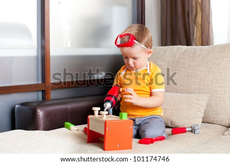 adorable child playing with wooden building toys at home