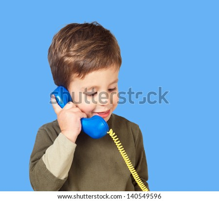 Adorable child talking on phone over blue background - stock photo