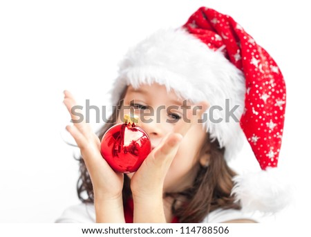 Adorable child wearing Santa Claus hat playing with a Christmas ball - stock photo