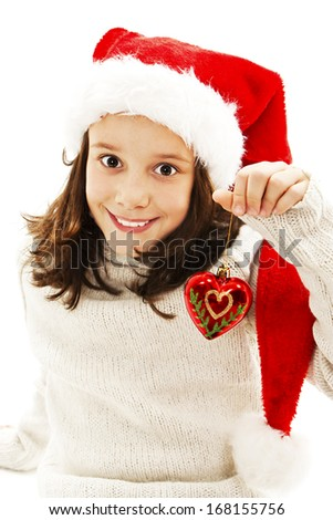 Adorable child wearing Santa Claus hat with a Christmas ball. Isolated on white background - stock photo