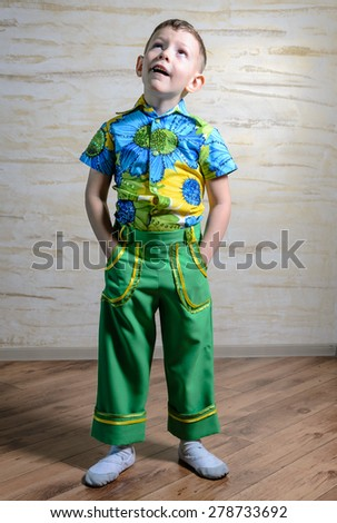 Adorable child wearing shirt with floral pattern and green pants while standing with hands in pockets and looking up with a funny inquiring expression, full length - stock photo