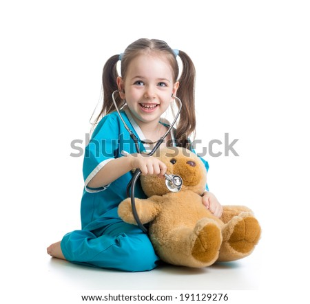 Adorable child with clothes of doctor examining plush toy over white - stock photo