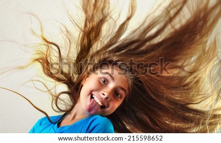 adorable child with long floating hair sticking her tongue out - stock photo