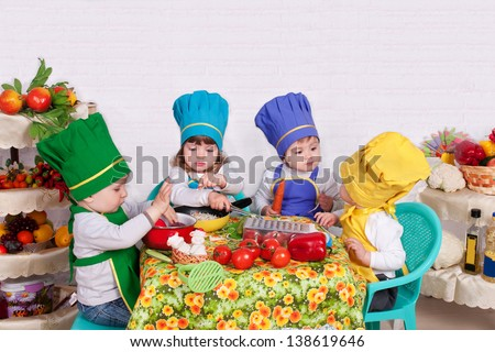 adorable children cooking in kitchen. little cute child in costume of Cook. Pretty beautiful boys and girls cook soup. baby boy. baby girl - stock photo
