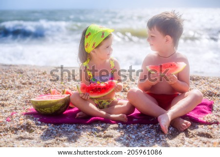adorable children eating watermelon on the beach