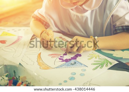 Adorable children,hand of children making decoration picture from colorful paper at home or school,kindergarten, pre-elementary school,make arts,vintage color,selective focus. - stock photo