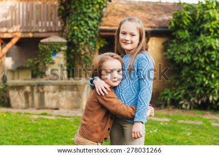 Adorable children hugging each other with lovely expression on their faces, outdoors - stock photo