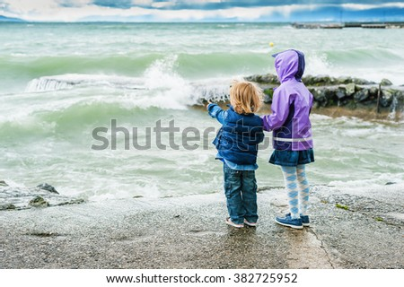 Adorable children playing next to lake on a stormy day, back view - stock photo