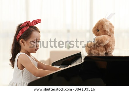 Adorable concentrated little girl playing the piano - stock photo