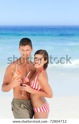 Adorable couple drinking a cocktail - stock photo