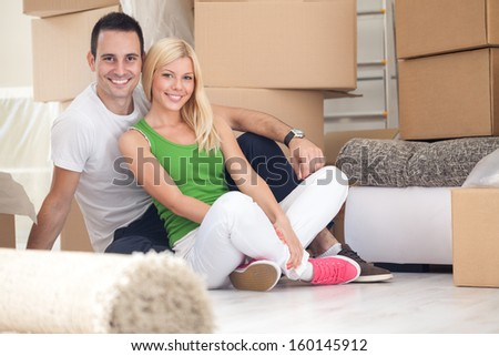 Adorable couple sitting on floor of their new home - stock photo