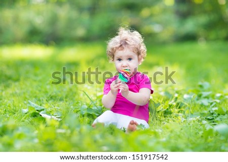 Adorable curly baby girl eating candy in a sunny summer park - stock photo