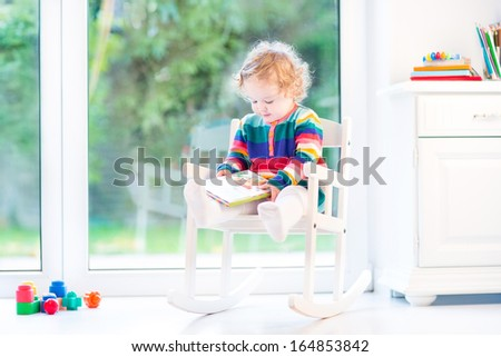 Adorable curly girl with curly hair wearing a colorful knitted dress reading in a white rocking chair next to a big window - stock photo