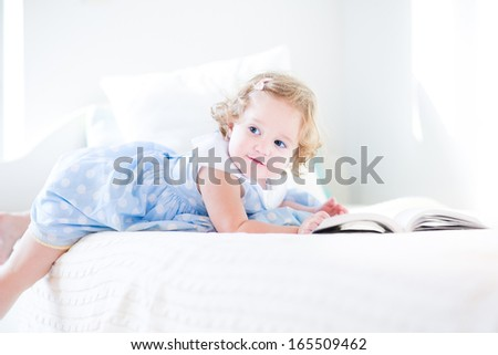 Adorable curly toddler girl in a blue dress reading a book at a white bed - stock photo