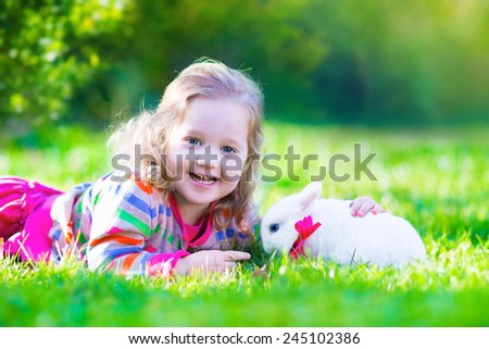Adorable curly toddler girl playing with a real rabbit in a sunny summer garden, child feeding bunny a carrot. - stock photo