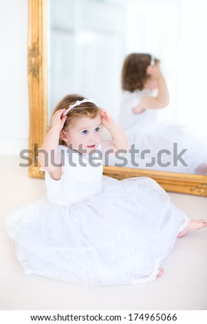 Adorable curly toddler girl trying on a beautiful white dress next to a big mirror - stock photo