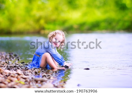 Adorable curly toddler girl wearing a blue dress playing at a river shore throwing stones into the water on a hot sunny summer day - stock photo