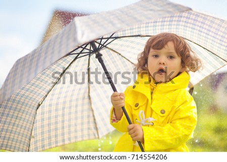 Adorable curly toddler girl wearing yellow waterproof coat holding big adult umbrella  under the rain in autumn day