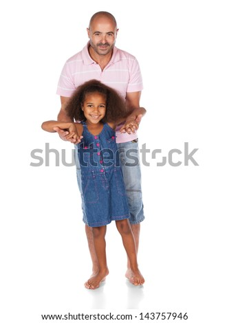 Adorable cute african child with afro hair wearing a denim dress is playing with her father. The dad is wearing a pink shirt and jeans.