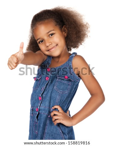 Adorable cute african child with afro hair wearing a denim dress. The girl is showing a thumbs up to the camera. - stock photo