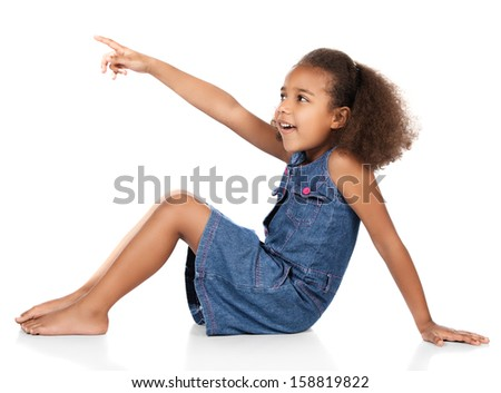 Adorable cute african child with afro hair wearing a denim dress. The girl is sitting and pointing away from the camera. - stock photo