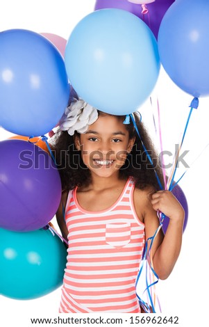 Adorable cute african child with afro hair wearing a white and pink striped dress. The girl is holding a bunch of bright coloured helium balloons. - stock photo