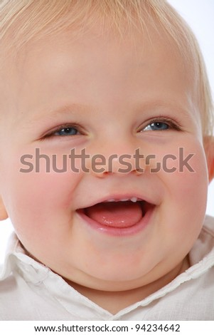 Adorable cute baby face pulling funny face and with new teeth laughing and smiling - stock photo