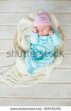 adorable cute baby girl sleeping in white basket on wooden floor - stock photo