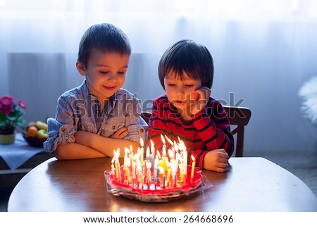 Adorable cute boys, blowing candles on a birthday cake at home - stock photo