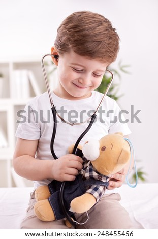 Adorable cute child with stethoscope of doctor examining teddy bear  - stock photo