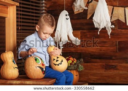 Adorable Cute Little Boy having fun in Halloween decorations - stock photo