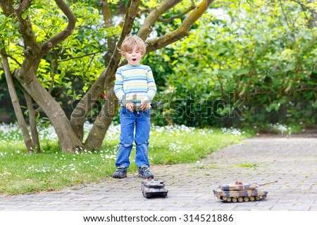 Adorable cute little child playing with toy tank, outdoors. Happy kid boy having fun on sunny summer day. Leisure, lifestyle for kids concept. - stock photo